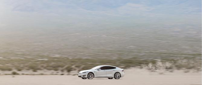 Bílá Tesla model S jede krajinou.