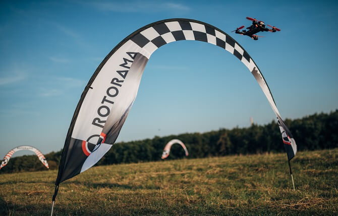 létání se závodními drony na louce