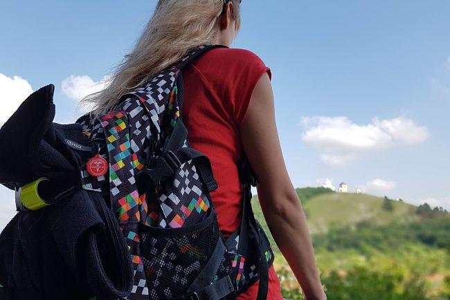 Turistka s URGENT ID na batohu.